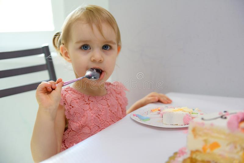 Baby girl 1 year old eating birthday cake in room. Birthday party. Childhood stock photos