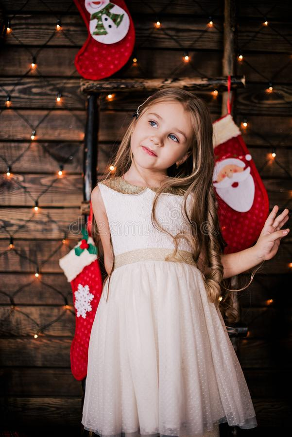 Baby girl 4-5 year old posing in room over christmas tree with decorations. Looking at camera. Merry christmas. Wearing stylish dr. Ess royalty free stock photography
