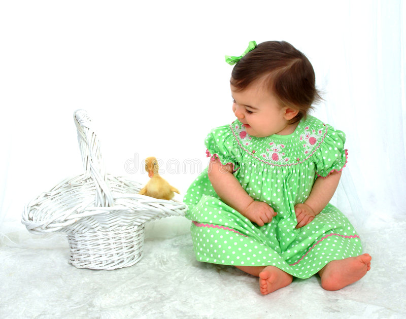 Baby Girl and Yellow Duck. Baby girl sitting beside wicker basket looking at duck perched on basket in front of white background royalty free stock image