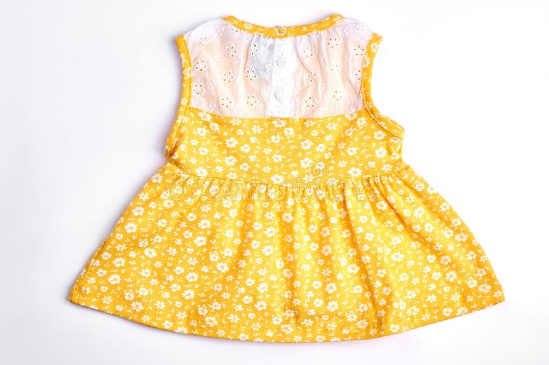 Baby-girl yellow patterned dress. royalty free stock photography