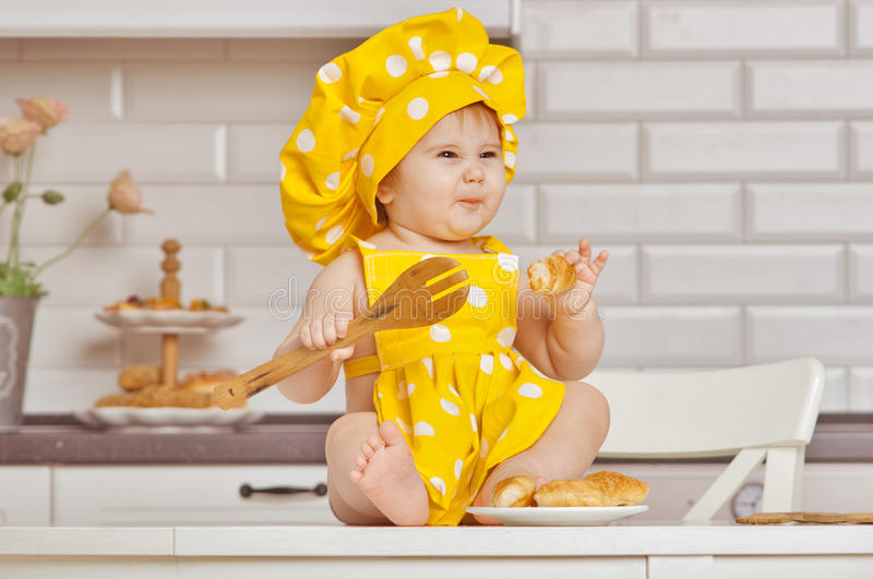 Baby girl in a yellow, spotty suit of the cook stock photography