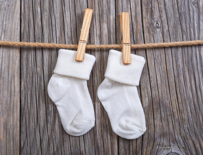 Baby goods hanging on the clothesline. Baby white socks on a clothespin royalty free stock images