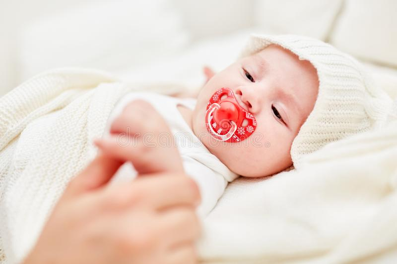 Baby grabs the thumb of an adult royalty free stock photography