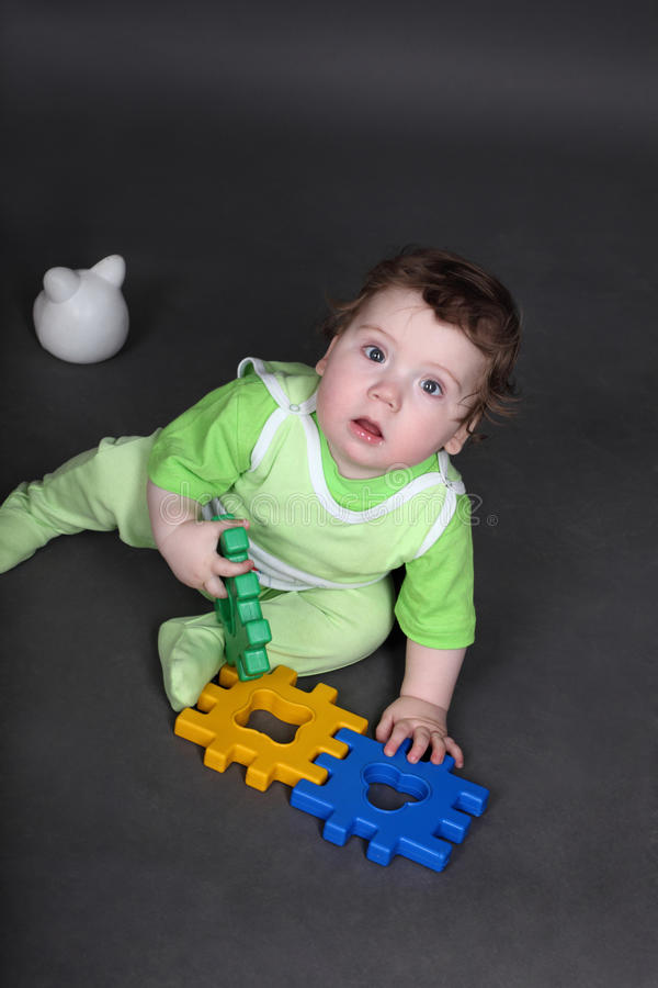 Baby in green crawlers sitting on floor. With toys royalty free stock images