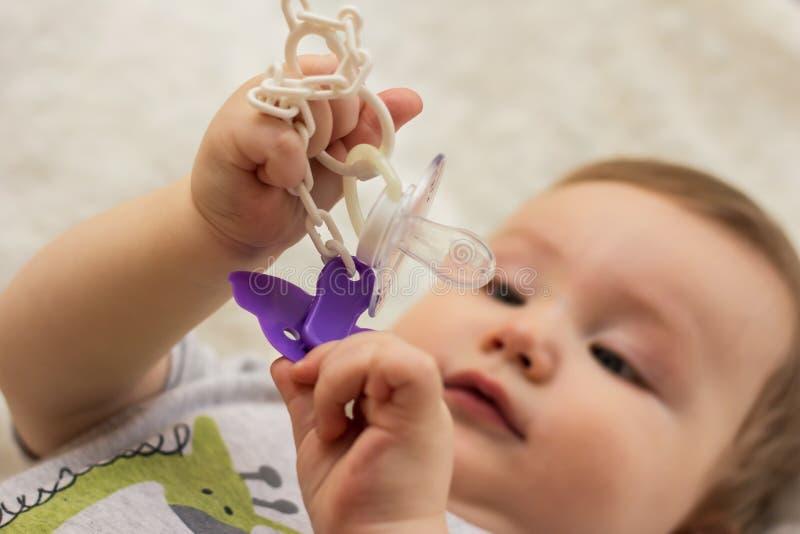 Baby hält Friedensstifterclip für Nippel stockbild