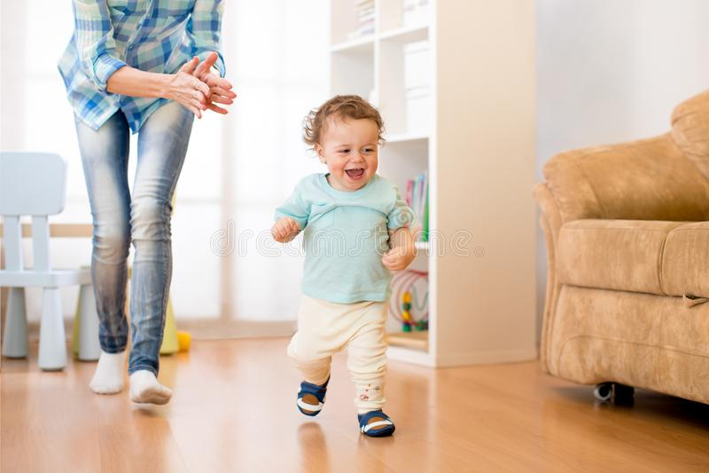 Baby haben einen Spaß, der im Wohnzimmer mit seiner Mutter läuft stockfotografie