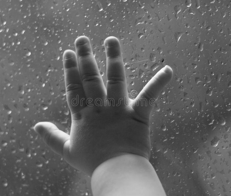 Baby hand against a window in the rain. Baby hand against a glass window with raindrops stock image