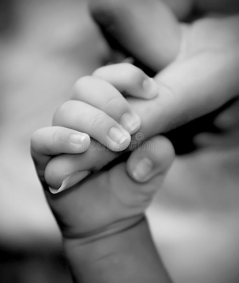 Baby hand holding mother's finger royalty free stock image