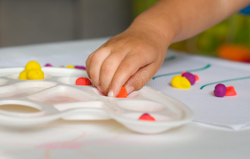 Baby hand and plasticine royalty free stock photo