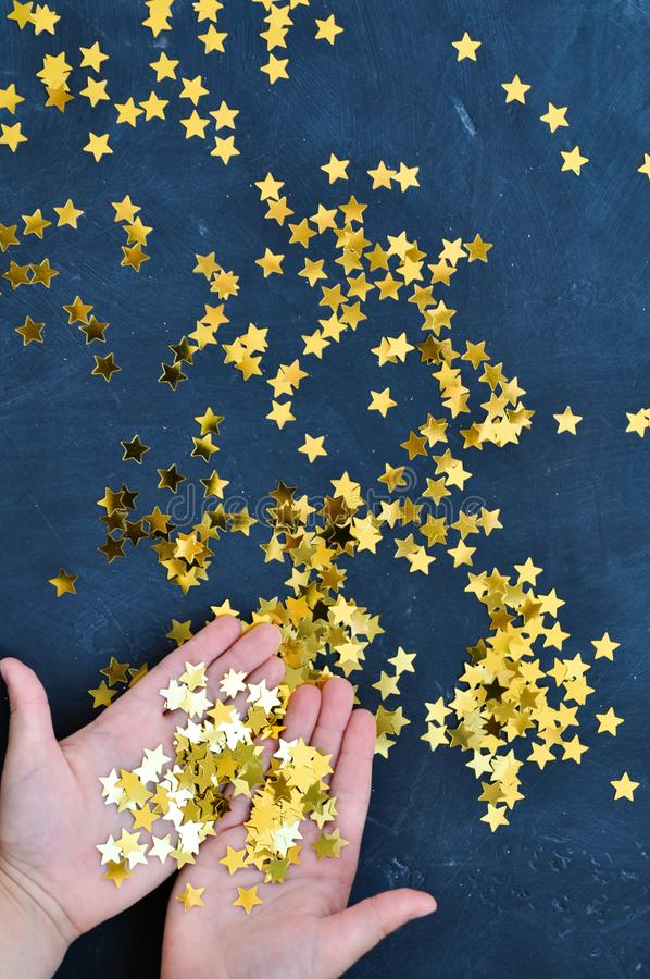 Baby hands holding shiny gold star confetti on a dark background in anticipation of Christmas and New year. Top view royalty free stock photos