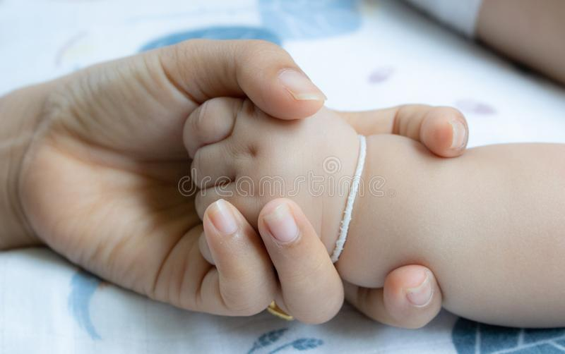 Baby hands in mother hands. Mom and her Child.Happy Family concept stock image
