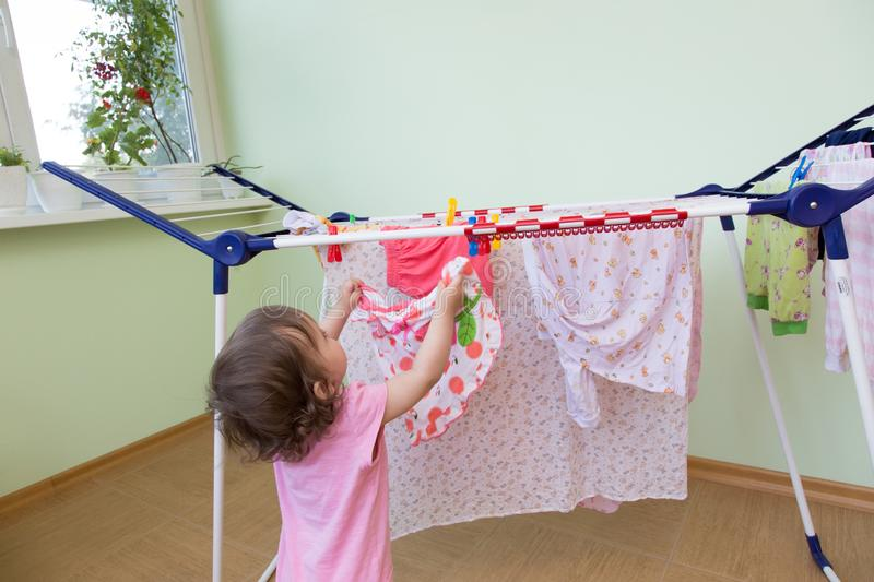 Baby hangs his wet clothes for drying on the balcony against the background of the lime wall. Concept little helper mom. Baby girld hangs his wet clothes for stock images