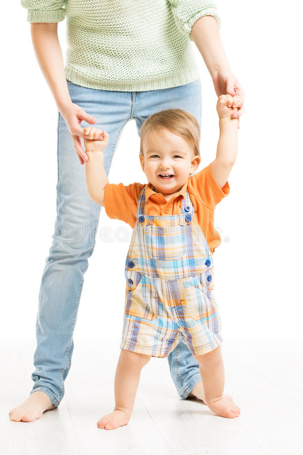 Baby Happy Go First Steps. Mother Helping Child Stock Photo