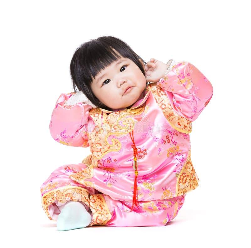 Baby har rolig ställing med den traditionella porslindräkten fotografering för bildbyråer