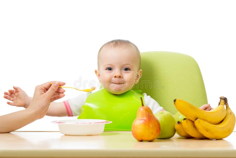 Baby having a table full of healthy food. Cheerful toddler with fruits apples, bananas, pear. Isolated on white stock photos