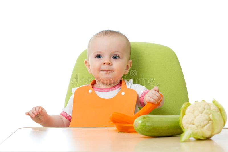 Baby having a table full of healthy vegetables. Cheerful toddler eating raw carrot. Isolated on white royalty free stock photography