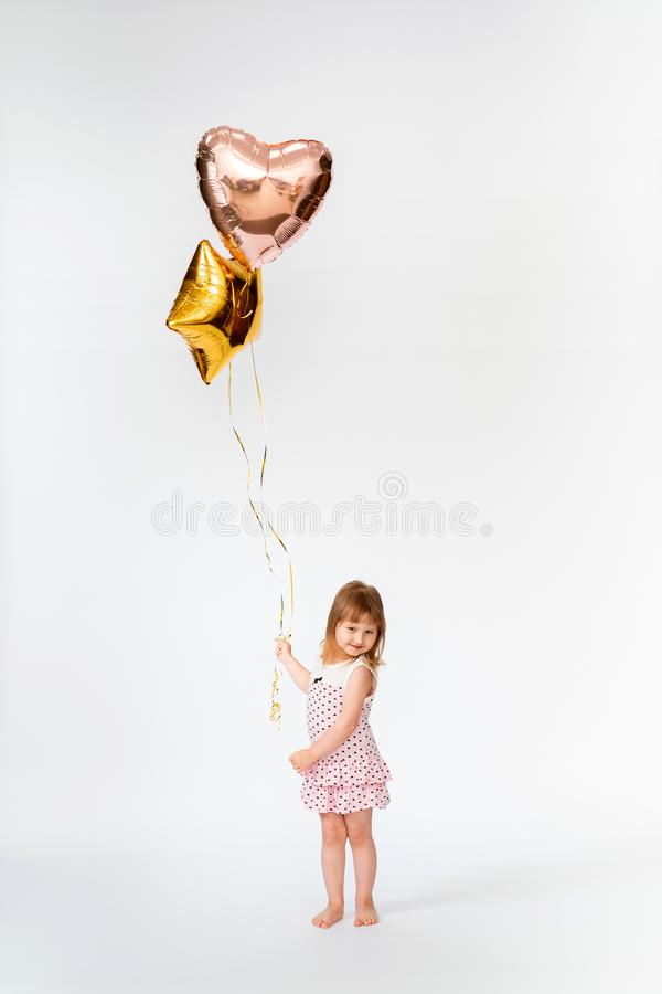 Baby with heart shaped balloons stock photo