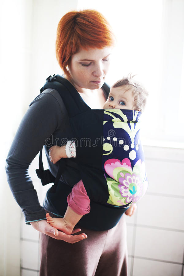 Baby held by his mother in a baby carrier stock photo