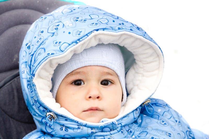 Baby het gelukkige lachen genietend van een gang in een sneeuwzitting van het de winterpark in een warme wandelwagen met schapehu stock afbeeldingen