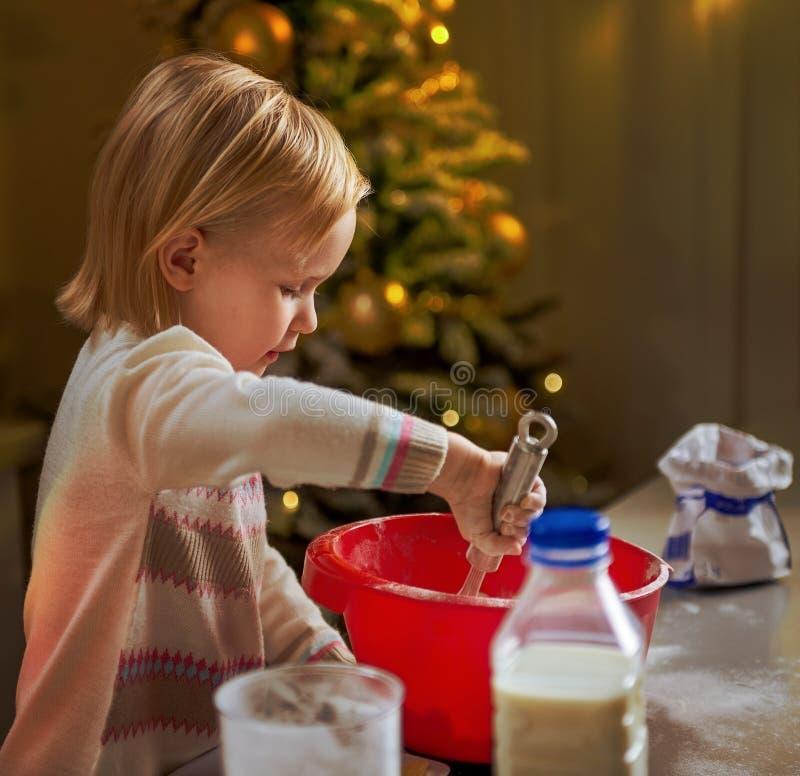Baby het kneden deeg in Kerstmis verfraaide keuken royalty-vrije stock foto
