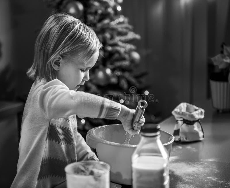 Baby het kneden deeg in Kerstmis verfraaide keuken royalty-vrije stock afbeelding