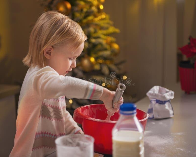Baby het kneden deeg in Kerstmis verfraaide keuken stock afbeeldingen