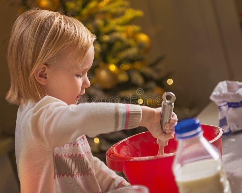 Baby het kneden deeg in Kerstmiskeuken stock fotografie