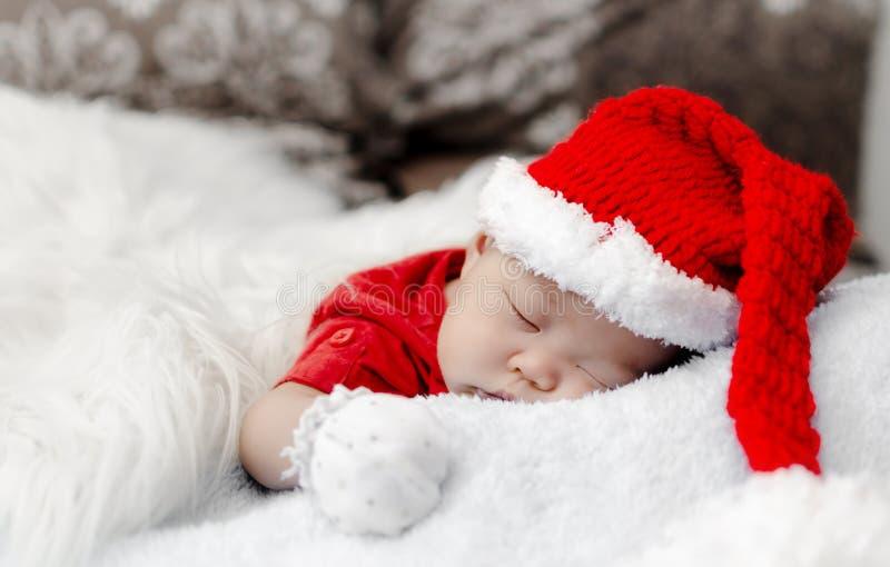 baby in het kostuumslaap van Kerstmissanta op bed royalty-vrije stock foto's