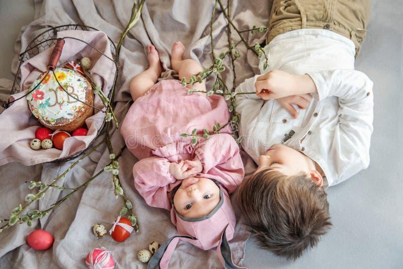 Baby het liggen op linnendeken en het dragen van een hoed in de vorm van een Paashaas met haar broer dichtbij eierenwilg vertakke royalty-vrije stock afbeeldingen