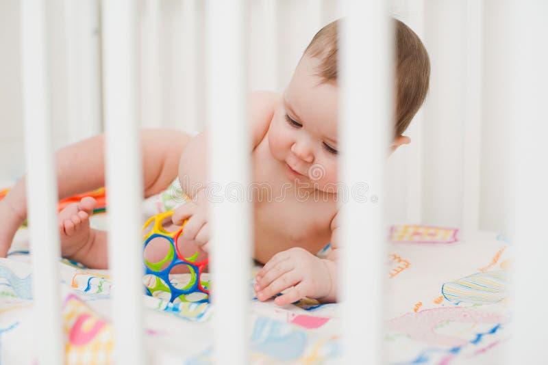 Baby het spelen in een voederbak stock fotografie