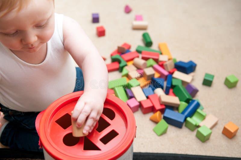 Baby het spelen met blokken en sorterende vormen stock afbeelding