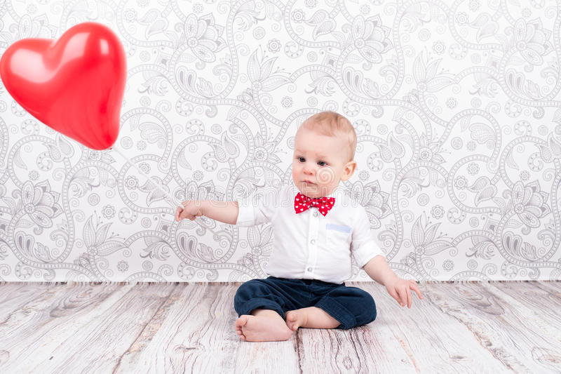 Baby het spelen met rode ballon stock afbeelding