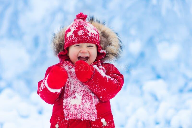 Baby het spelen met sneeuw in de winter stock afbeeldingen