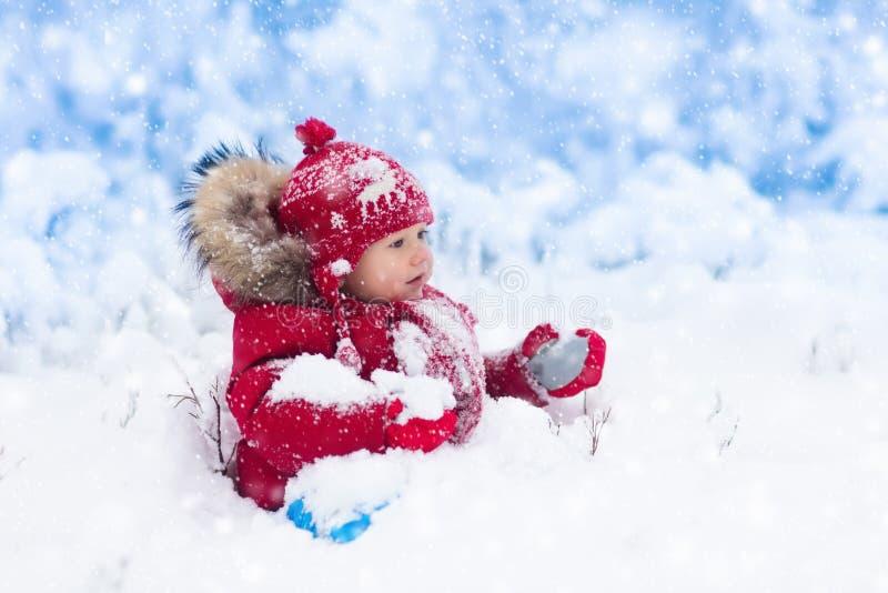 Baby het spelen met sneeuw in de winter stock afbeelding