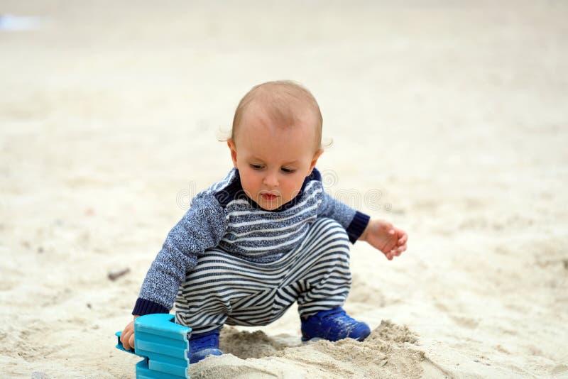 Baby het Spelen met Zand en Blauwe Plastic Schop op het Strand stock foto