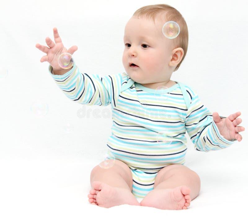 Baby het spelen met zeepbels stock fotografie