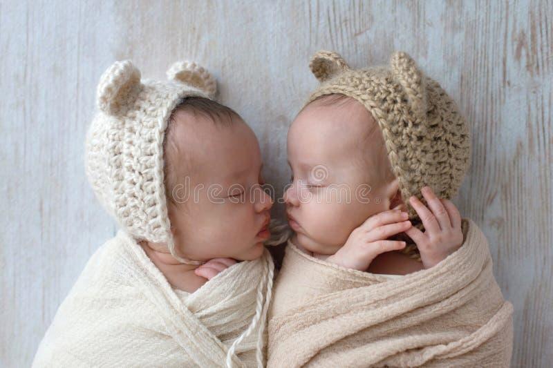 Baby het Tweelingmeisjes draagt Dragen Bonnetten stock afbeeldingen