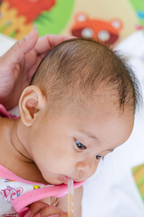 Baby het voeden met mineraal zoutdrank, gezondheidszorgconcept royalty-vrije stock afbeelding