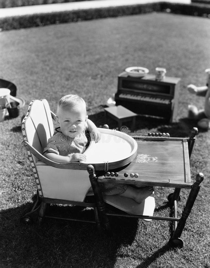 Baby in highchair outside stock image