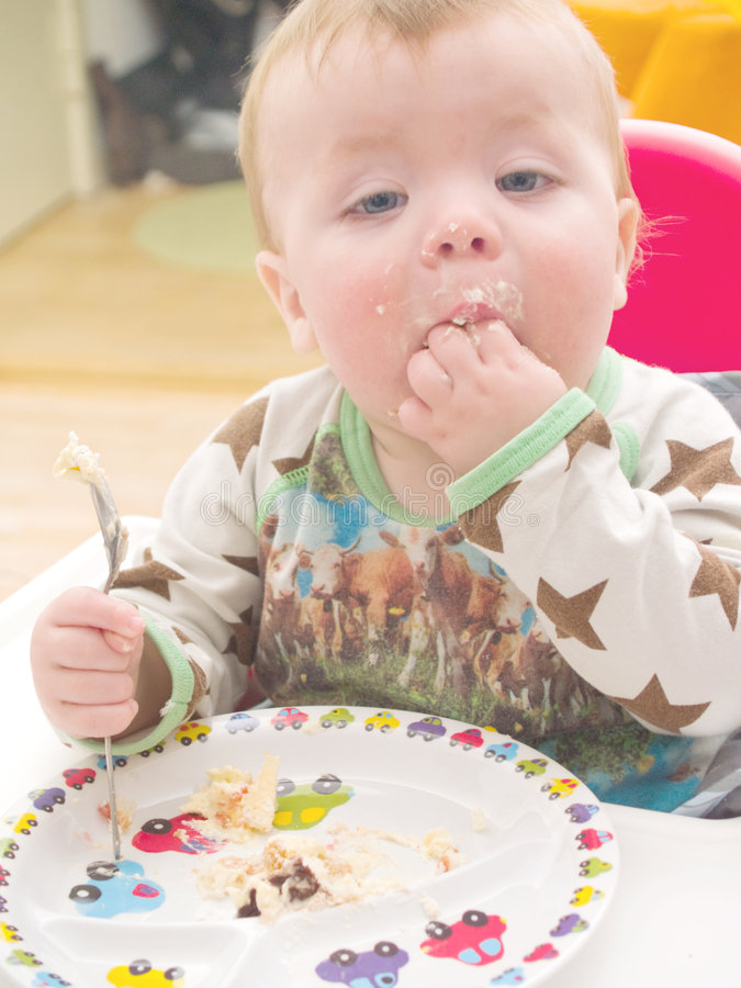 Baby on his first birthday eating cake. Cute baby toddler on his first birthday eating cake royalty free stock image