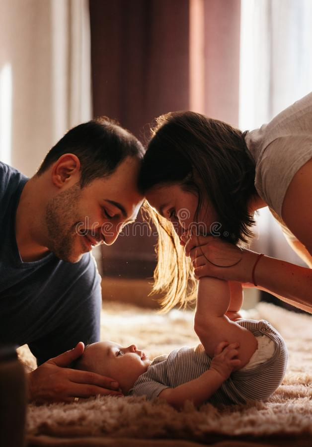 Baby with his parents playing on the bed. Happy family at home. Lifestyle cozy photos. Little boy 4 months old royalty free stock photo
