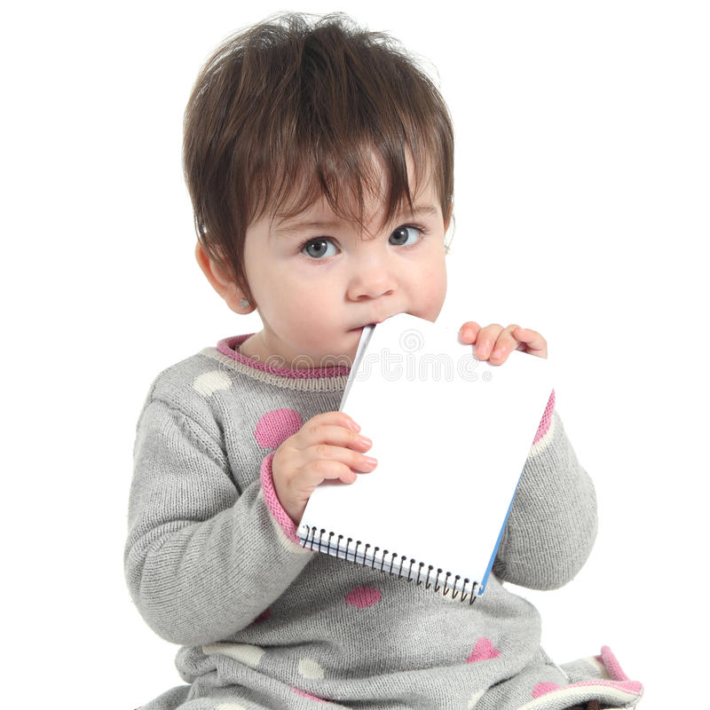 Baby holding and biting a blank notebook. On a white isolated background royalty free stock photos
