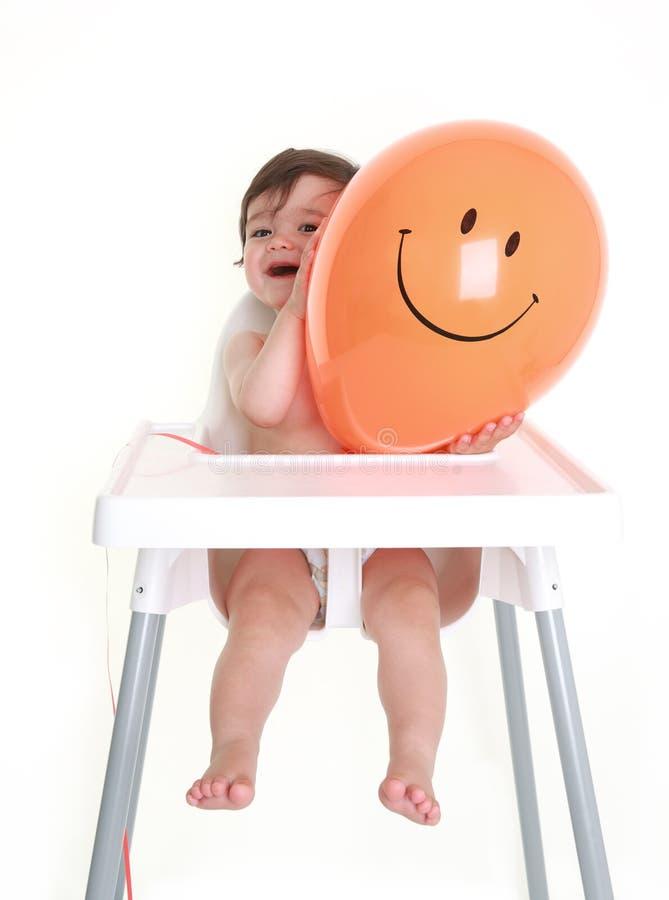 Baby holding happy balloon stock image