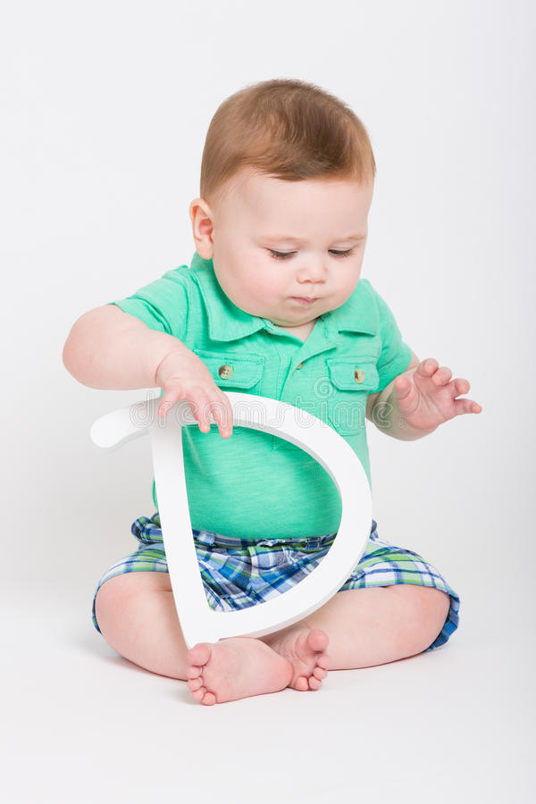 Baby Holding Letter D Looking Down royalty free stock photos