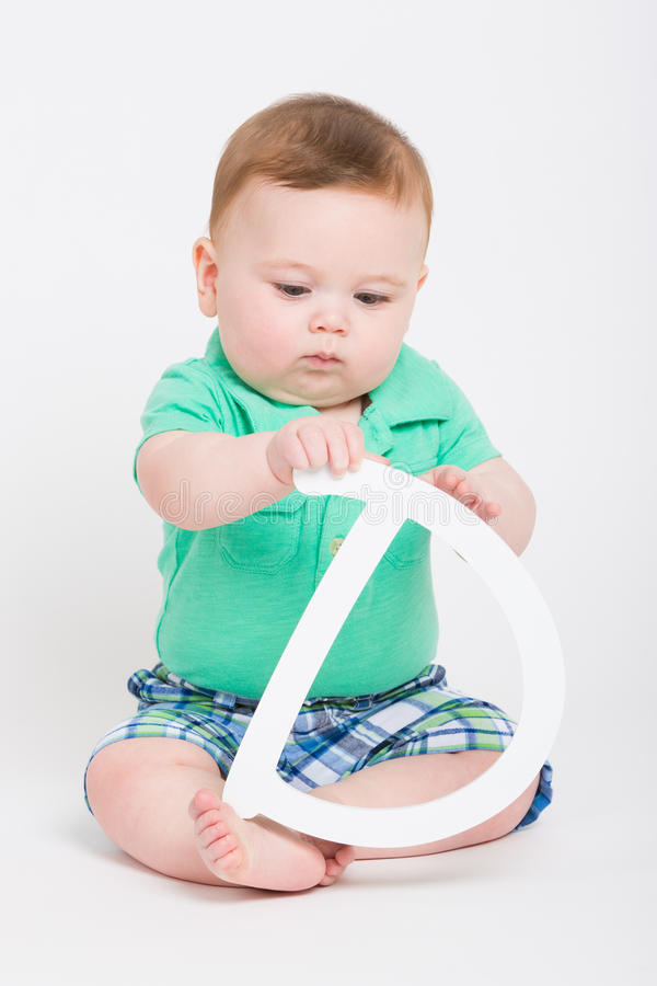 Baby Holding and Looking at Letter D royalty free stock photos