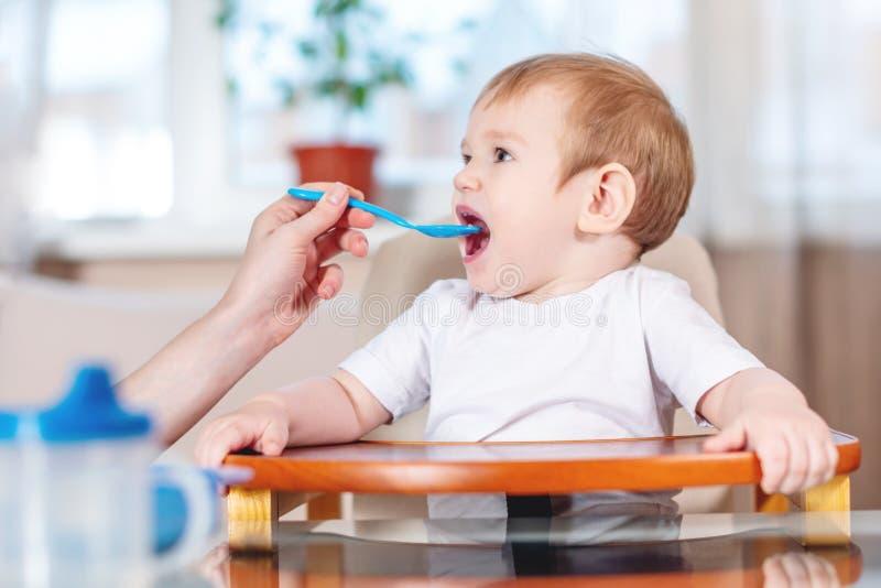 BABY-Holdinghand der Mutter Fütterungsmit einem Löffel des Breis Gefühle eines Kindes beim Essen der gesunden Nahrung stockbild