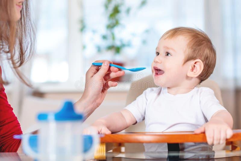 BABY-Holdinghand der Mutter Fütterungsmit einem Löffel des Breis Gefühle eines Kindes beim Essen der gesunden Nahrung lizenzfreie stockfotografie
