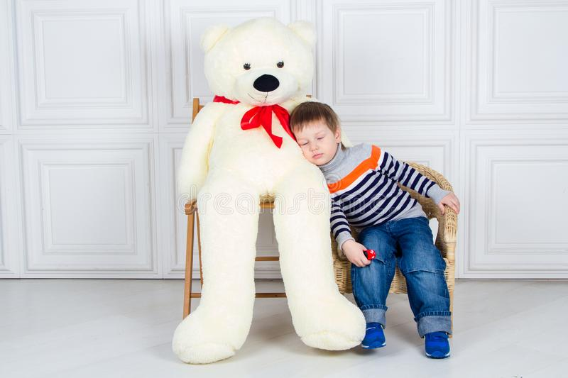 Baby hugging with a huge Teddy bear. Boy sitting on the chair, close eyes. White background stock photo