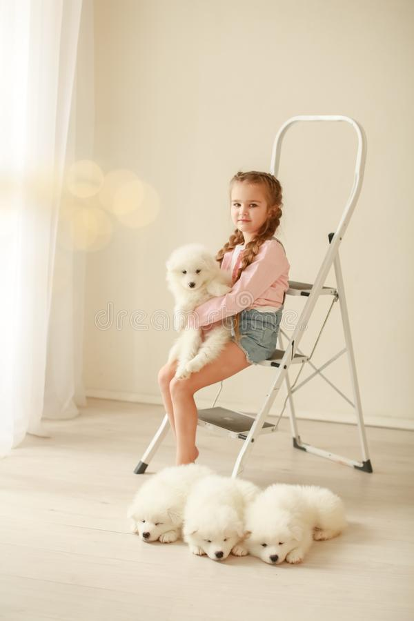 Baby Hugs the white fluffy puppy. Kids.  stock photography