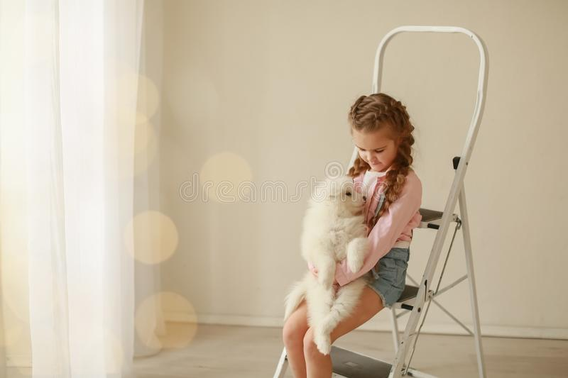 Baby Hugs the white fluffy puppy. Kids.  stock photos